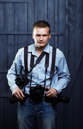 correspondent: young handsome man photographer with serious face in shirt with many photo cameras equipment of journalist or reporter professional in studio on wooden background