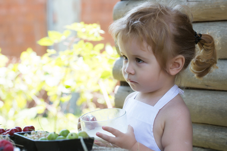 ponytail: Cute little boy with blond hair ponytail in white pinafore drinks milk on summer day on wooden background Stock Photo