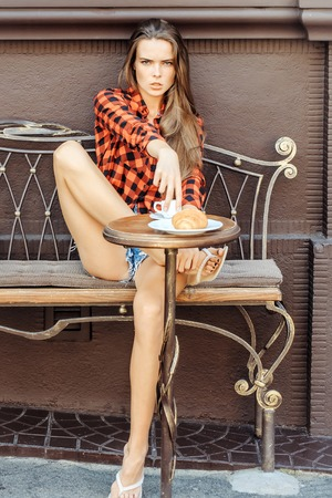 pretty slim model girl with long legs sits in red checkered shirt and shorts on vintage coach in coffee cafe