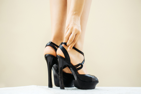 fastens: Woman hand fastens strap on black shoes fancy high heel pumps strappy sandals on her beautiful legs feet on white floor