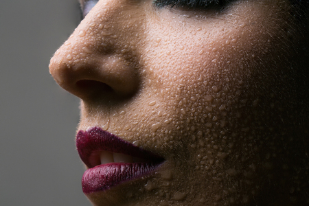Beautiful woman with water drops and purple lips makeup on young fresh face skin on grey background