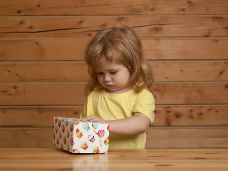 opens: Cute little boy child with long blond hair opens colorful paper box with sweet cakes dessert at wooden table