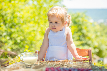 pinafore: Cute little boy in white pinafore sits in high chair at table with cup of milk on sunny summer day on natural background