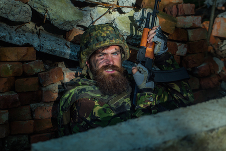 grime: Man soldier with dust grime beard and angry on his face in helmet and war camouflage and rifle in his hands sitting in brick stone ruins Stock Photo