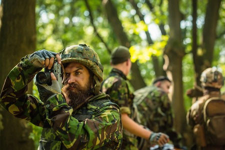 grime: Young soldier man with beard on grime serious face in ar?y ammunition and helmet holding camera in his hands on background of soldiers in forest