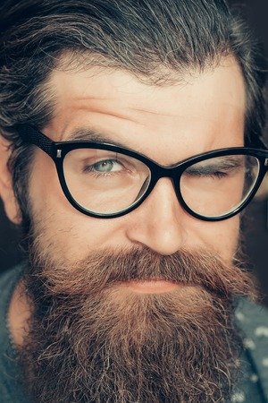 Handsome man hipster with long beard moustache and graying hair winks his eye in glasses on dark wall