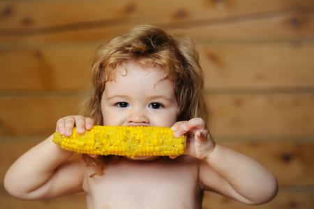 bare chest: Small boy child with long blonde hair eating yellow corn or maize with bare chest and funny face on wooden or wood background Stock Photo