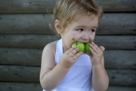 pinafore: Cute little boy blond in white pinafore eats two green apples on summer day on wooden background Stock Photo