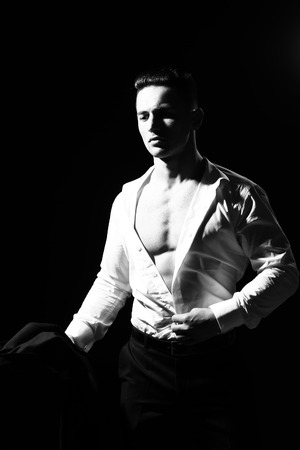 young handsome gentleman undressing fashion white shirt with sexy bare muscular torso in studio, black and white