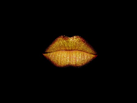 beautiful female closed lips or mouth gold or golden color with gloss or glittering lipstick isolated on black background Reklamní fotografie
