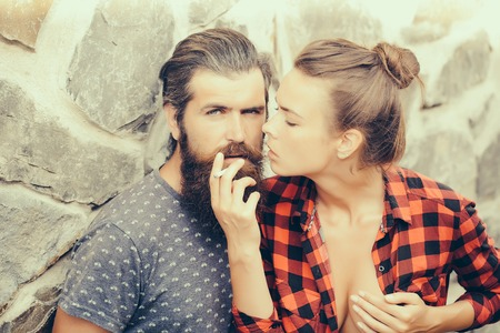Young couple of handsome bearded man with long beard smoking cigarette and sexy woman in checkered shirt outdoor on stony wall background