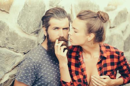 joven fumando: joven pareja de hombre con barba y guapo con barba larga cigarrillo fumar y mujer atractiva en camisa a cuadros al aire libre en el fondo de la pared de piedra Foto de archivo