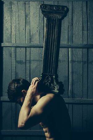 atlantes: Atlantes support, power. Young man with muscular body holding hard column. Stock Photo