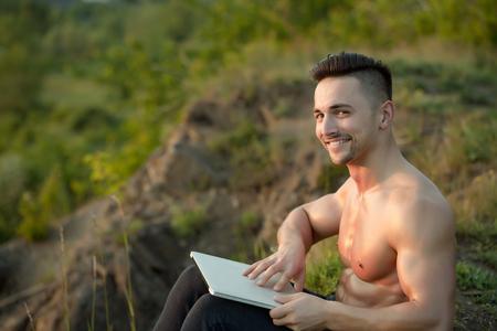 nackte brust: Junger stattlicher lächelnder Mann mit dem muskulösen sexy Körper und nackte Brust mit dem Laptop im Freien sonnigen Tag sitzt