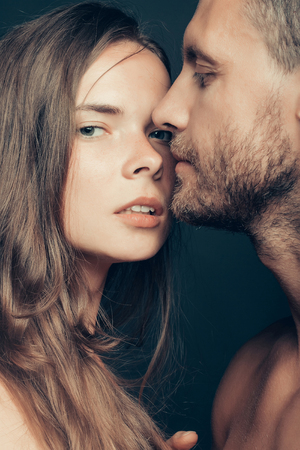 young unshaven: young couple of woman or girl with pretty face and long hair embrace handsome muscular unshaven man Stock Photo