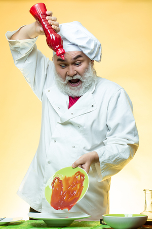 catsup bottle: Bearded chef with ketchup bottle and emotional face in white uniform and hat on yellow background