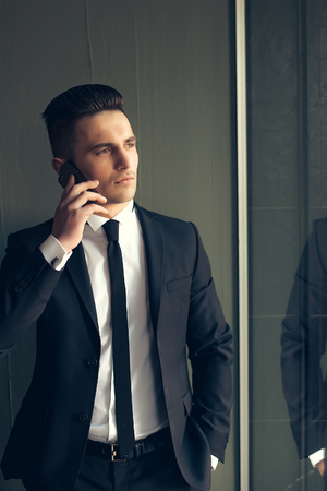 conversaciones: Man young handsome sensual elegant model in suit with skinny necktie open coat talks on mobile phone looks away hand in pocket reflects in mirror on grey background
