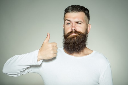 long beard: handsome young man with long beard and moustache on face with super gesture showing thumb up on grey background in studio