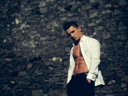 poses de modelos: El hombre joven y guapo modelo sensual con el torso desnudo en la camisa blanca se abría posturas abiertas con las manos en los bolsillos del pantalón negro se ve en la cámara al aire en el fondo de mampostería