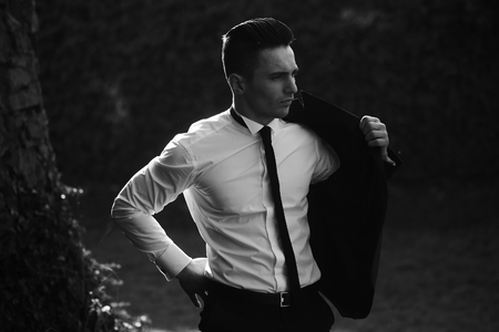 puts: Man young handsome elegant model in white shirt puts on suit coat with skinny necktie outdoor on landscape black and white on natural background Stock Photo