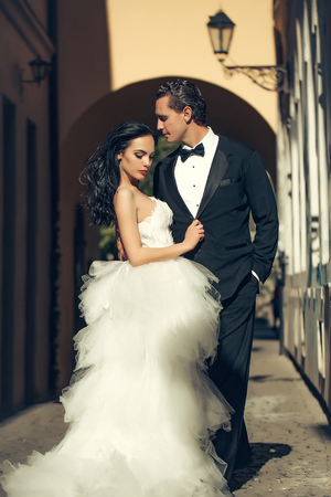 desire: young wedding couple of sexy girl with brunette hair and pretty face in white bride dress and handsome man in black groom suit standing near street lamp of building arch sunny outdoor