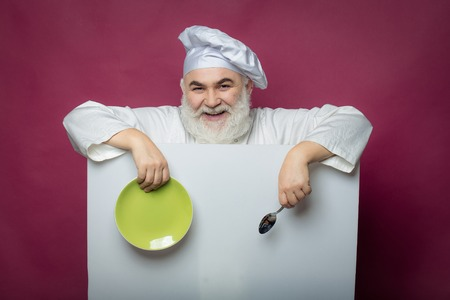 servilleta de papel: Happy bearded cook holding blank paper with spoon bottle and napkin on yellow background, copy space Foto de archivo