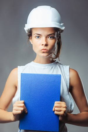 exercise book: Young woman forewoman engineer with serious pretty face in building white helmet holding blue exercise book posing on grey background studio