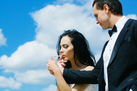 gas lighter: Elegant man offers to woman beautiful brunette gas lighter to light cigarette for smoking on blue sky