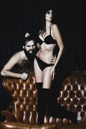 relaciones sexuales: Pareja joven con la muchacha atractiva y un hombre guapo en el sofá. personas adultas, las relaciones