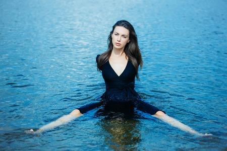 beine spreizen: junges Mädchen in der Marine Kleid mit langen dunklen Haaren sitzt im Wasser mit gespreizten Beinen Lizenzfreie Bilder