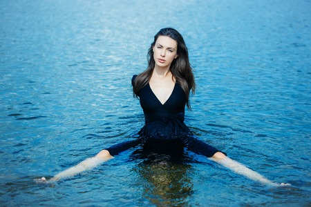 spread legs: young girl in navy dress with long dark hair sits in water with spread legs