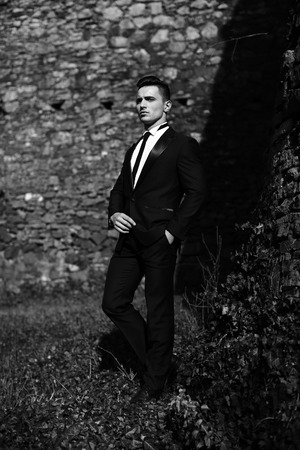 trouser: Man half face young handsome elegant model in suit with skinny necktie poses with hand in trouser pocket one leg backward outdoor black and white on masonry background