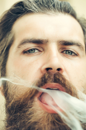 exhale: Young man hipster smoker with beard on face open exhale tobacco smoke from open mouth closeup