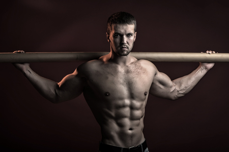 pectoral muscle: strong young man with muscular body in jeans holding iron crossbar standing posing in studio on red background, horizontal picture