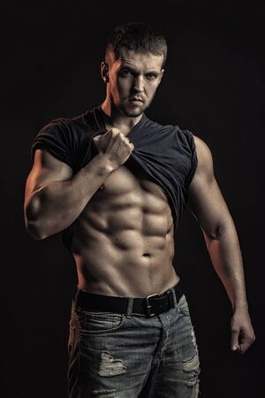 sexual anatomy: One handsome sexual strong young man with muscular body in blue jeans with shirt on shoulder standing posing in studio on black background, vertical picture Stock Photo