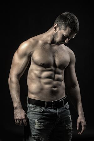 sterke jonge man met een gespierd lichaam in jeans naar uit staan poseren in studio op zwarte achtergrond, verticale foto Stockfoto