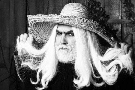 periwig: Bearded senior man in long white wig and straw round hat on wooden background, black and white Stock Photo