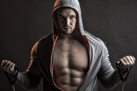 sexual anatomy: strong young man with muscular body in grey sport jacket with hood holding training device standing on studio black background, horizontal picture Stock Photo