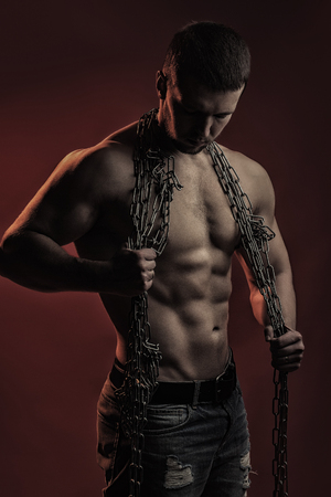 sexual anatomy: strong young man with muscular body in blue jeans holding rope with hands hanging on neck and shoulders standing posing in studio on red background, vertical picture