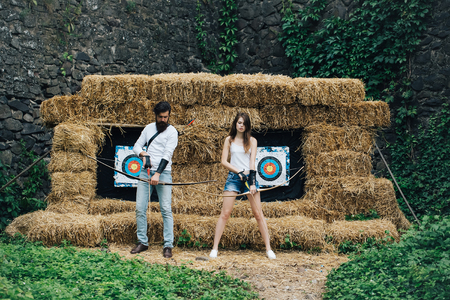 aims: Attractive couple stands with bow and arrow in front of the aims Stock Photo