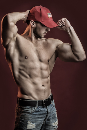 sexual anatomy: strong young man with muscular body in red sport cap standing posing in studio on red background, vertical picture