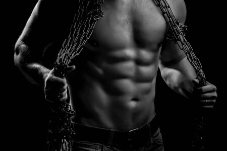 sexual anatomy: strong young man with muscular body in blue jeans holding rope with hands hanging on neck and shoulders standing posing in studio black and white, horizontal picture