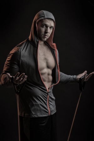 training device: young man with muscular body in grey sport jacket with hood holding training device standing on studio black background, vertical picture
