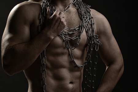 pectoral muscle: strong young man with muscular body in blue jeans holding rope with hands hanging on neck and shoulders standing posing in studio on black background, horizontal picture