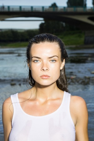 Young woman with pretty face in wet white shirt standing in sea on river water outdoor on natural background