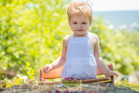 pinafore: Cute little boy in white pinafore eats fruit cake on high chair at table on sunny summer day on natural background