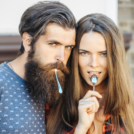 stylish men: young couple of pretty girl with long hair and handsome bearded man hipster with beard holding metallized tea spoon outdoor