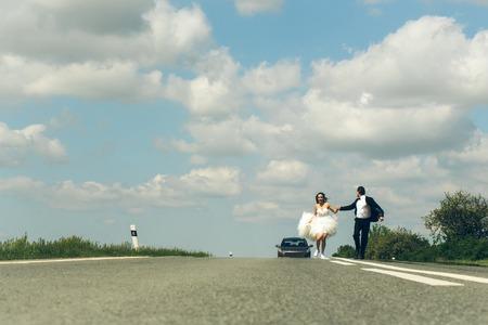 young wedding happy couple of sexy girl with brunette hair and pretty face in white bride dress and handsome man in black groom suit running on road way on cloudy blue sky background, copy space Stock Photo