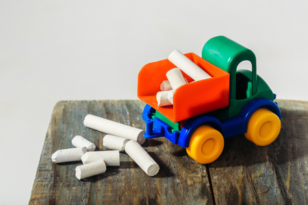 white chalks: Plastic colorful toy truck with white chalks on wooden board on white background
