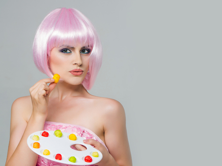 paletas de caramelo: sexy glamour girl or woman with fashionable makeup on pretty face and short hairstyle or pink wig in dress eating colorful marmalade sweets on paint palette in studio on grey background, copy space